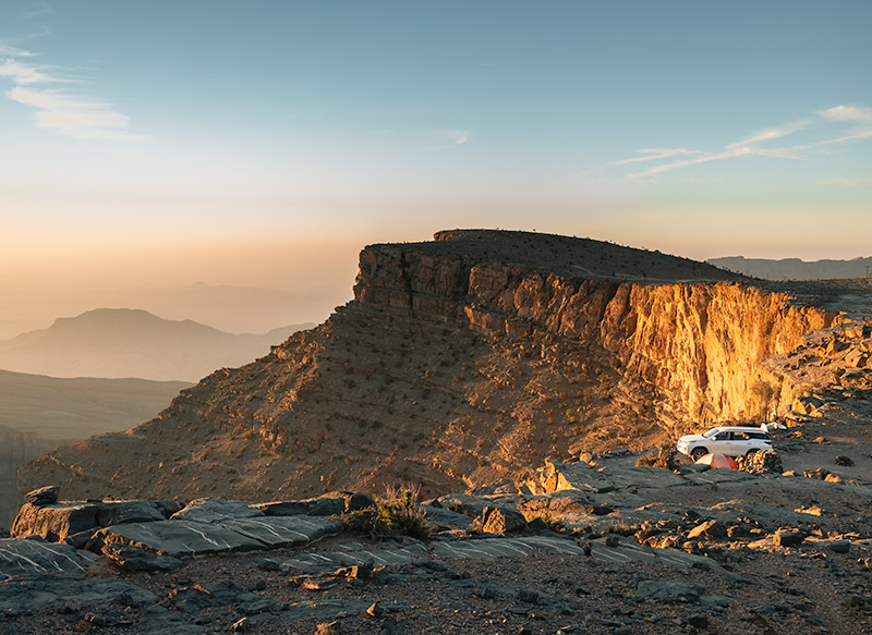 Golden sunrise light hits the wall of the Omani Grand Canyon below Jebel Shams. A 4WD and tent sits on the rim of the canyon.