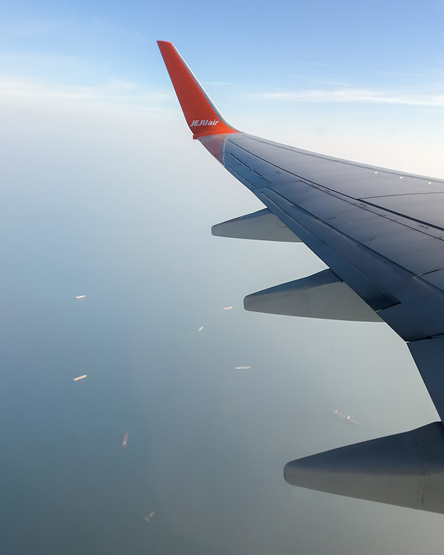 Looking out the window while flying over the ocean in Korea on budget airline Jeju Air
