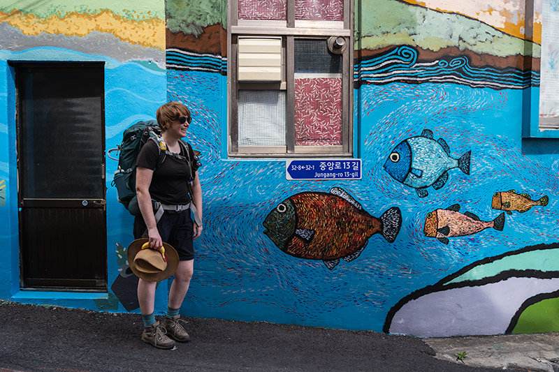A woman wearing hiking clothes and a backpack walks in front of a colourful mural wall in Jeju City, South Korea