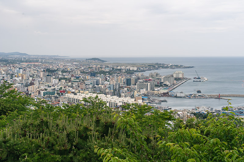 A view over Jeju City from the top of nearby Sara-bong hill, with tall apartment buildings and the ocean in view