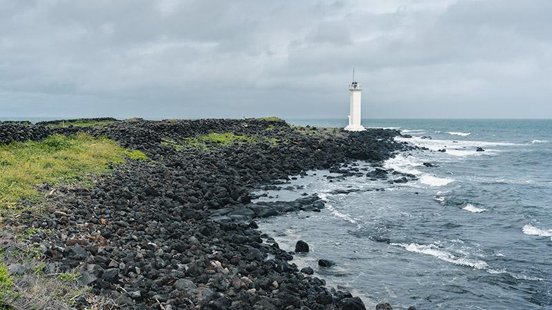 A white lighthouse along the rocky black volcanic shore of Jeju Island