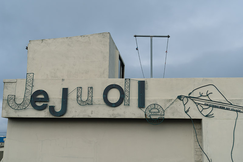 The words 'Jeju Olle' and a hand holding a pencil are made out of wire and attached to the side of a white house in Gimnyeong Village, Jeju Island