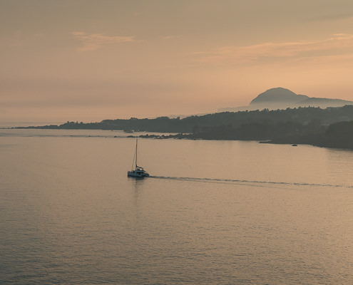 A catamaran sails on the calm water at sunset off the south coast of Jeju Island