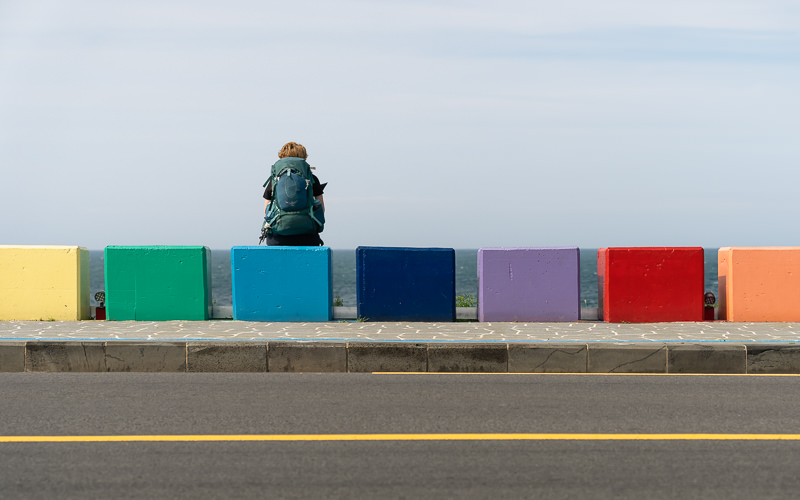 A person sits on one of many multicoloured blocks along a footpath in front of the sea on the north coast of Jeju Island