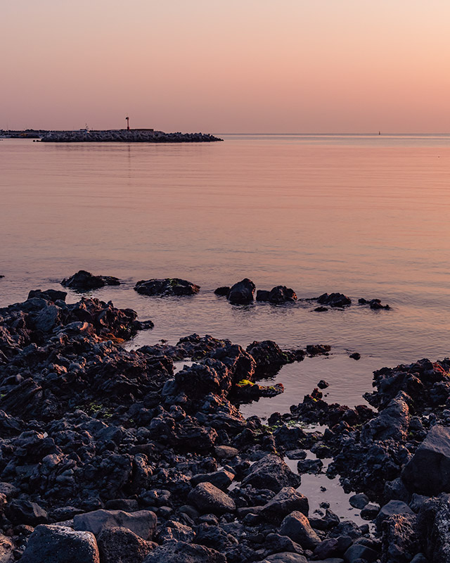 A sunset shot of black volcanic rocks with a small lighthouse in the distance