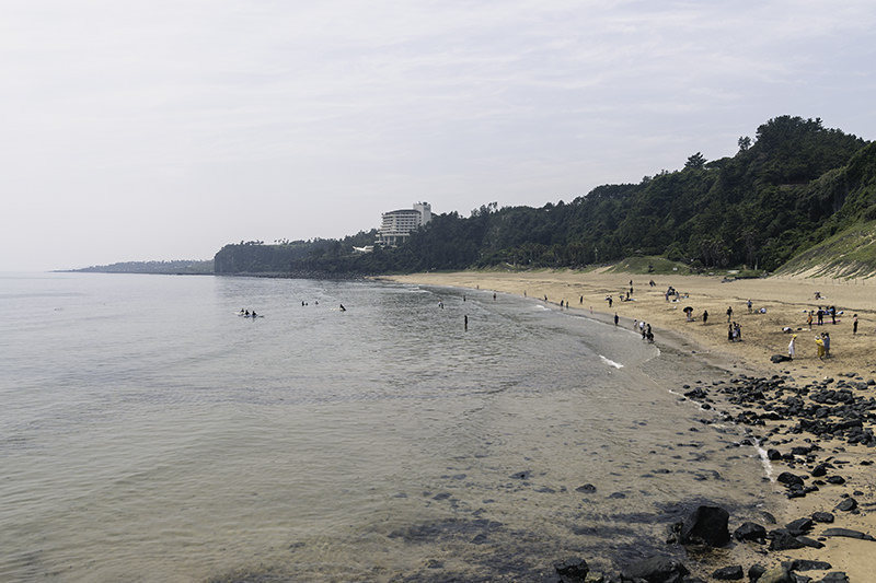A view of Jungmun Beach from the east, with people relaxing on the sand and surfers in the water