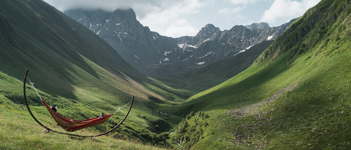 A person relaxes in a hammock with a wide view of Juta Valley and the Chaukhi Massif in the Kazbegi area of Georgia