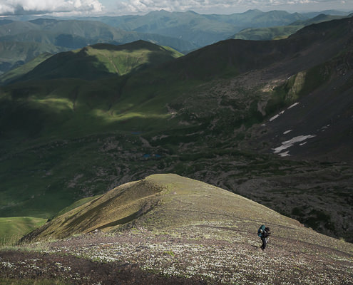 A hiker descends the switchback ridgeline trail from Chaukhi Pass to Abudelauri Lakes on the Juta to Roshka trek in Georgia