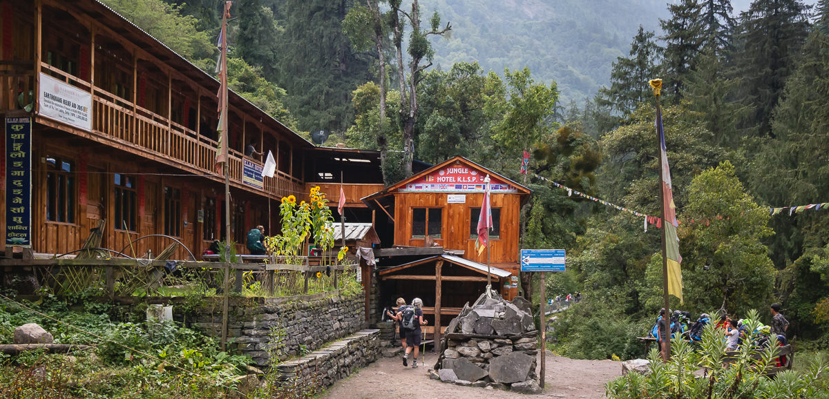 A two storey wooden lodge in a forest clearing on the Manaslu Circuit Trek