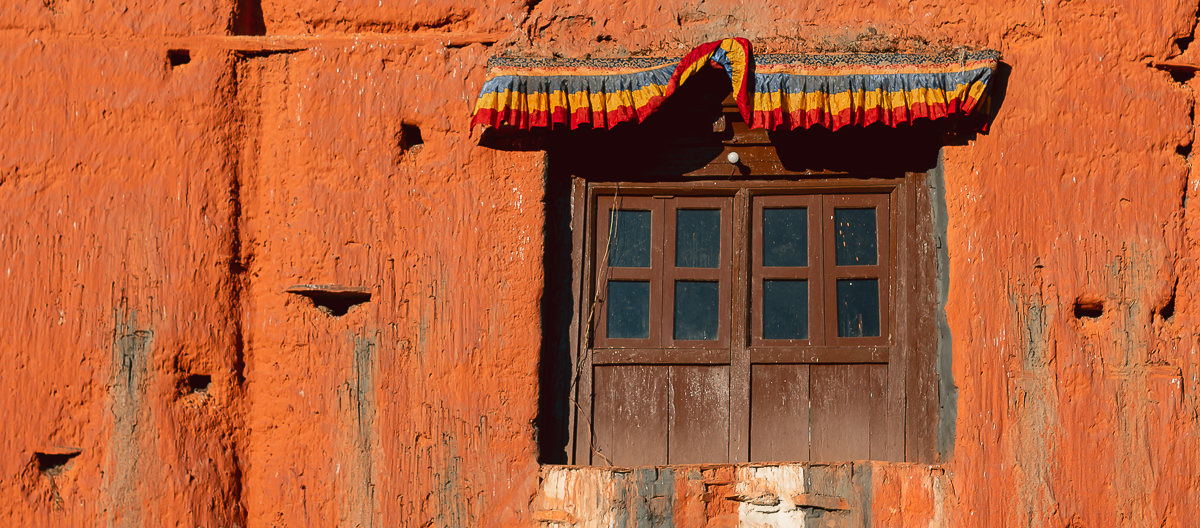 A small wooden window set in the red mudbrick wall of the Kag Chode Thupten Samphel Ling Gompa in Kagbeni