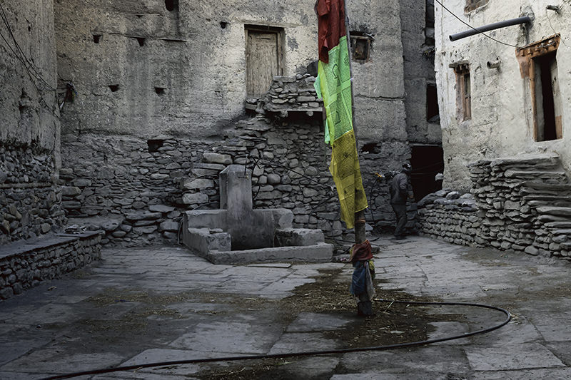 An enclosed courtyard with prayer flags in the middle and mudbrick houses on all sides in the medieval village of Kagbeni