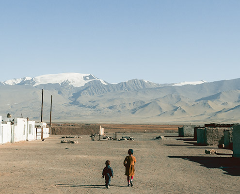 Two small kids wandering the wide dusty streets of Karakul in northern Tajikistan
