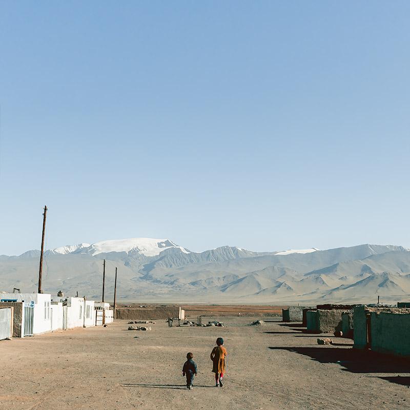Two small kids wandering the wide dusty streets of Karakul in northern Tajikistan