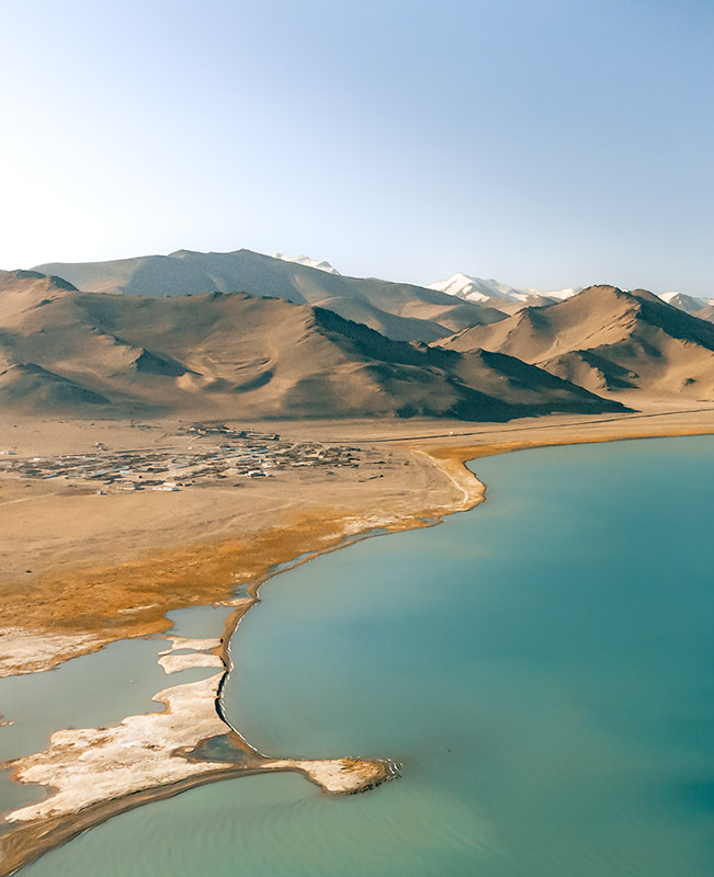 A drone image of Karakul lake and village, a blue expanse surrounded by snowy peaks along the Pamir Highway