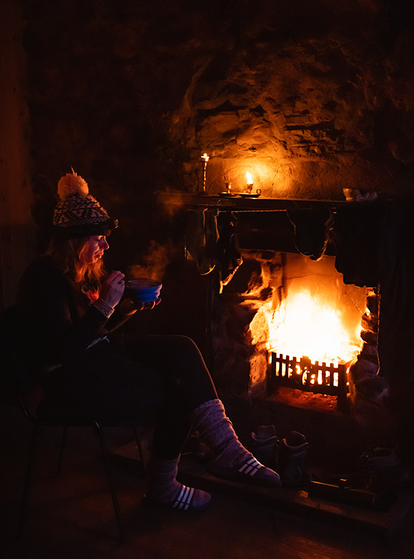 Tucking in to some tasty food and staying warm by the fire in Gleann Dubh-Lighe Bothy
