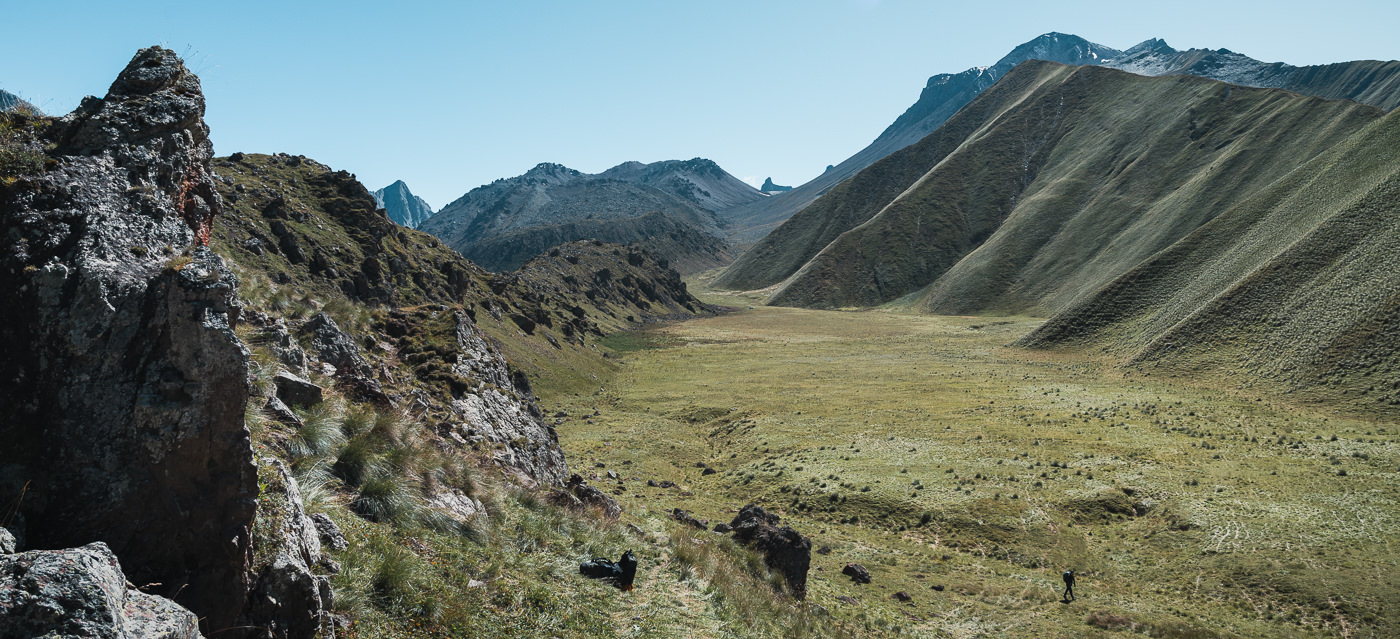 A wide grassy meadow surrounded by hills and mountains on the Keli plateau, the ideal place to camp on Day 1 of the Kelitsadi Lake Trek
