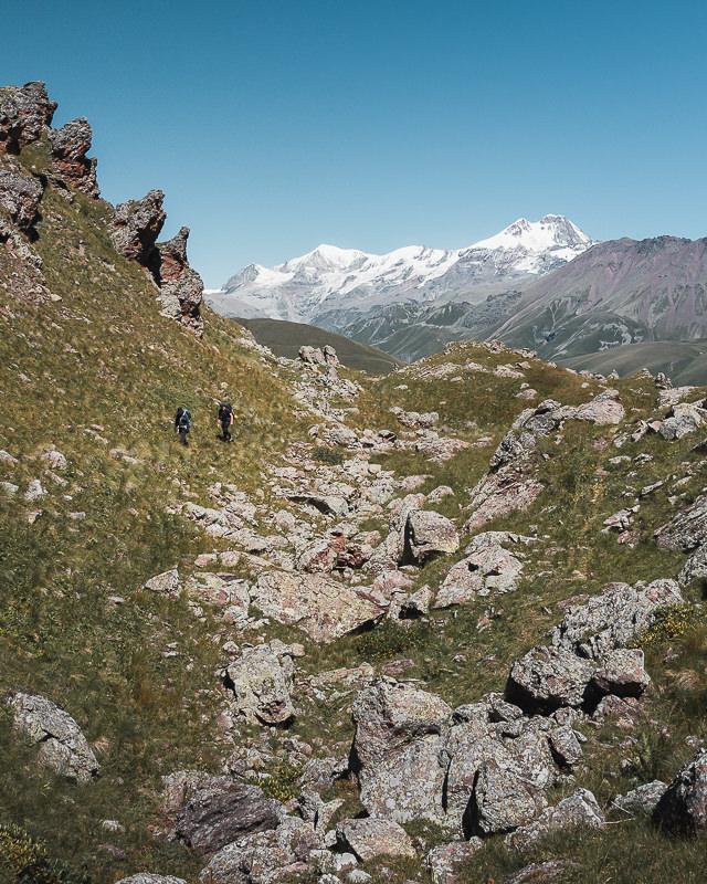 Two hikers climb gradually past jumbled rocks with Mt Kazbek marking the skyline behind, on the Kelitsadi Lake Trek in Georgia