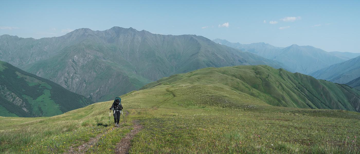 A hiker climbs the gradual track on the wide and grassy Khidotani Ridge on the Shatili Omalo trek in Georgia