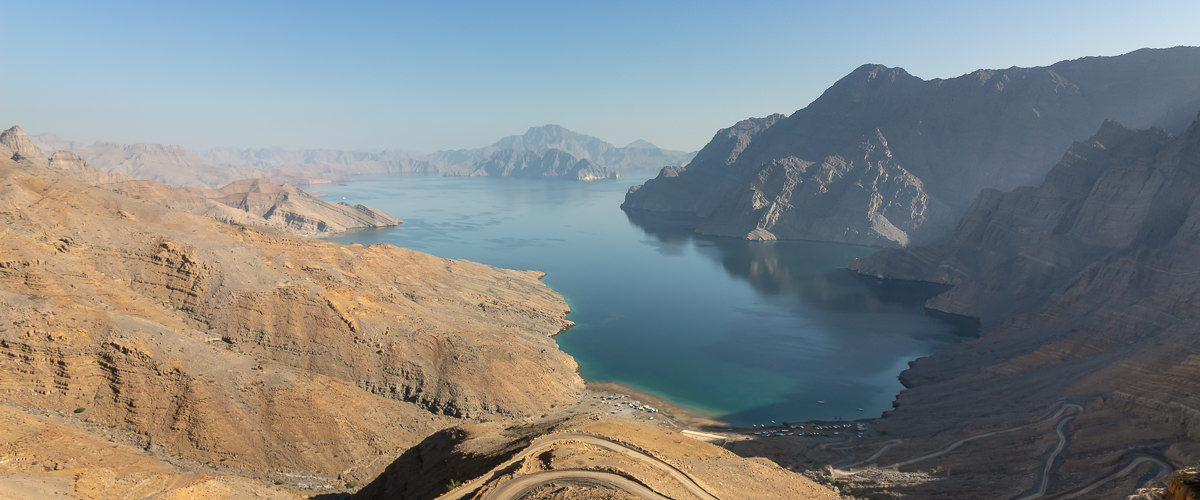 The cobalt blue perfectly still Khor Najd in Musandam, Oman, the surrounding mountains reflected in the water