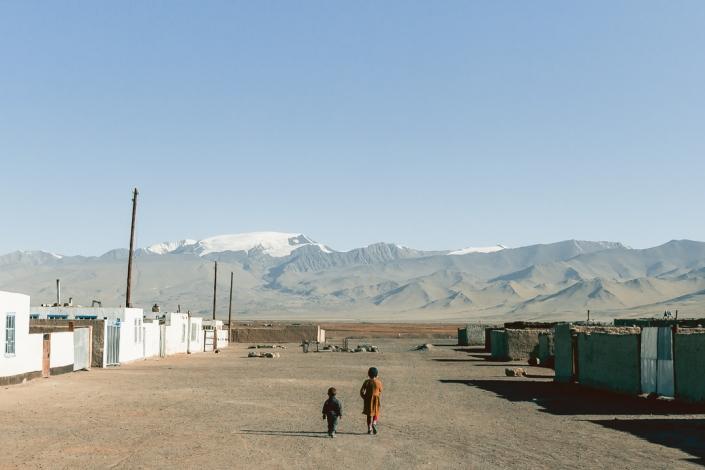 A couple of kids wandering the empty streets of Karakul in Eastern Tajikistan in the early morning sun.