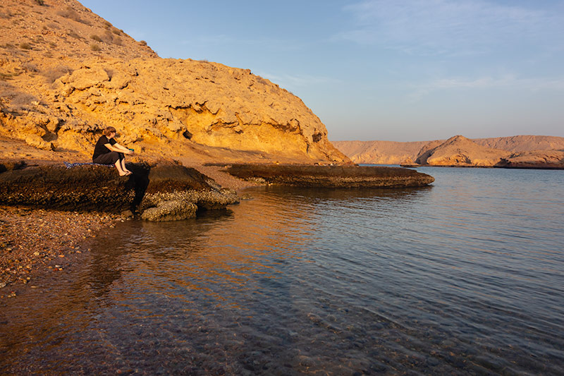 Kim admiring the inlet and sun drenched sandy rocks at Bandar Al Khiran, one of the best campsites in Oman.