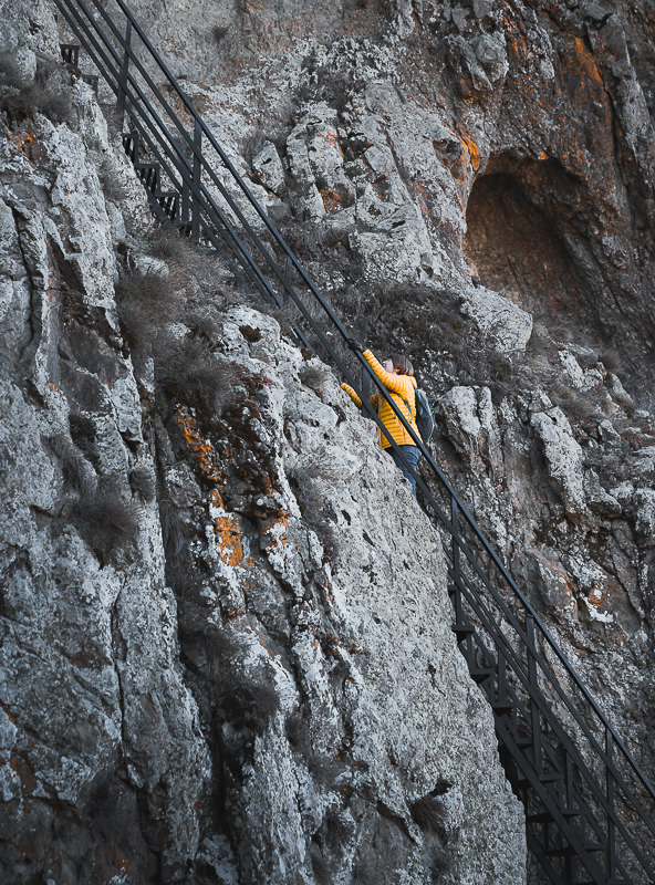A person climbs to Kojori Fortress on the steep metal staircase bolted to the rock face
