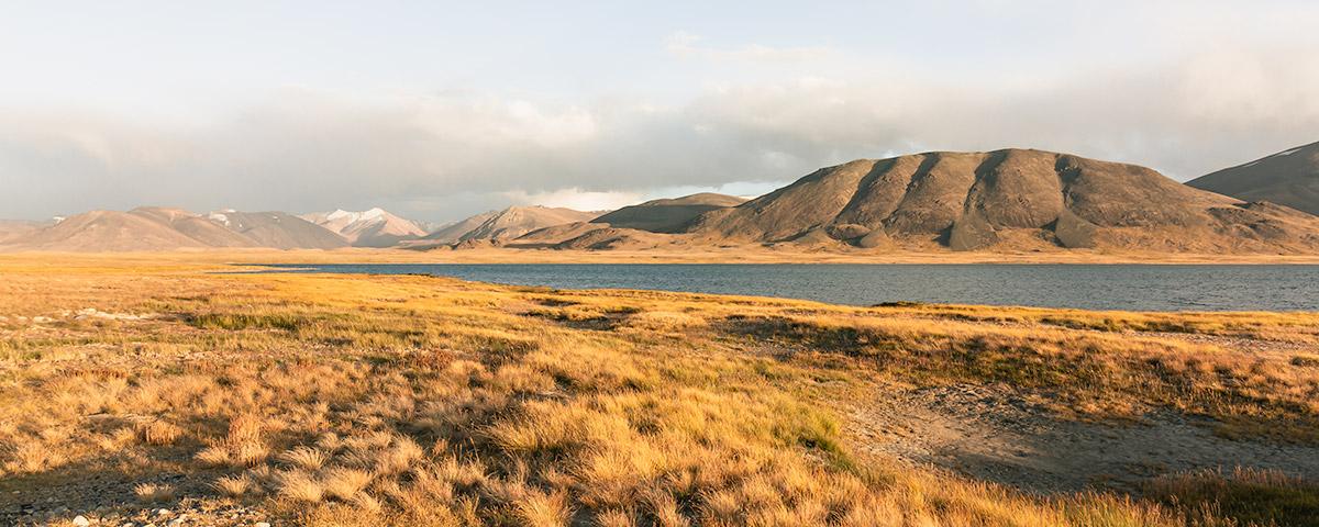 Kokjigit Lake glowing golden at sunset, mountains rising behind