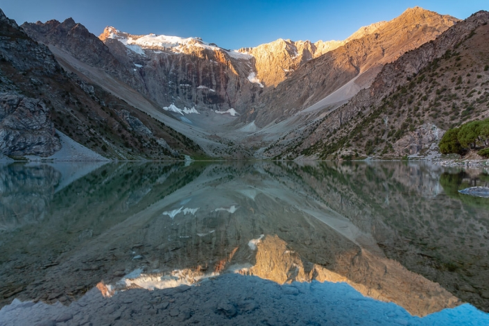 Sunrise at Kulikalon Lake in the Fann Mountains of Tajikistan. Fed by glacial meltwater, this is the biggest of three lakes in an amphitheatre-like valley, surrounded on all sides by mountains.