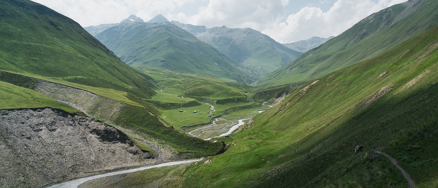 A wide valley view looking down on Kvakhidi Meadows and the Kvakhidistskali River from the Shatili Omalo trail