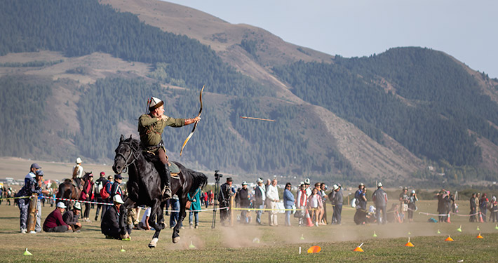 A traditionally dressed horse back archer looses an arrow from a galloping black horse in front of admiring crowds at the World Nomad Games in Kyrgyzstan