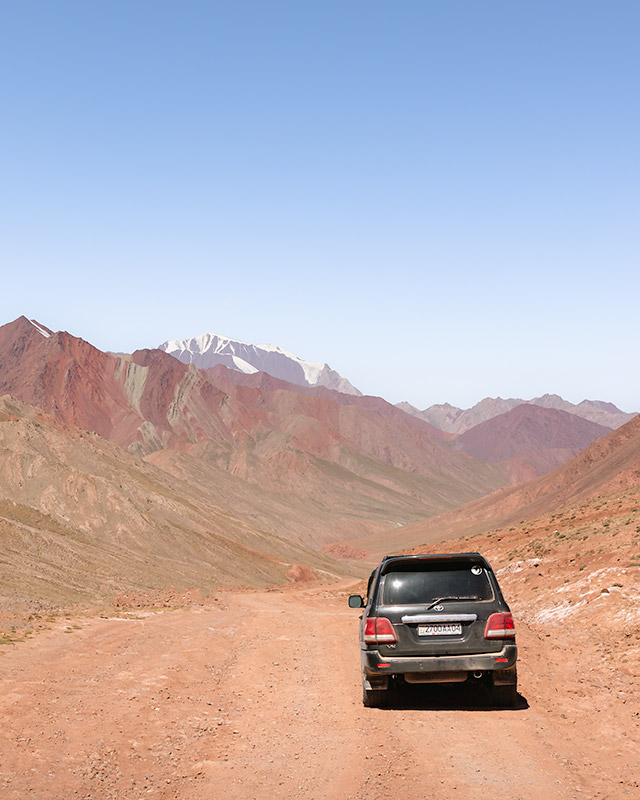 A black Landcruiser driving towards colourful mountains in no man's land between Bordobo Border Crossing, Kyrgyzstan, and Kyzylart Border Crossing in Tajikistan on the Pamir Highway