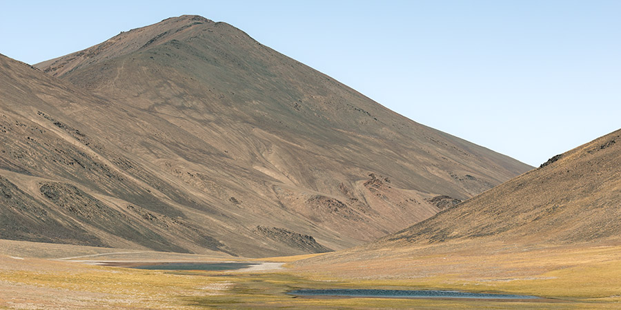Two small lakes sit below a mountain as the dirt track winds down towards Jarty Gumbez on a Pamir Highway Road Trip