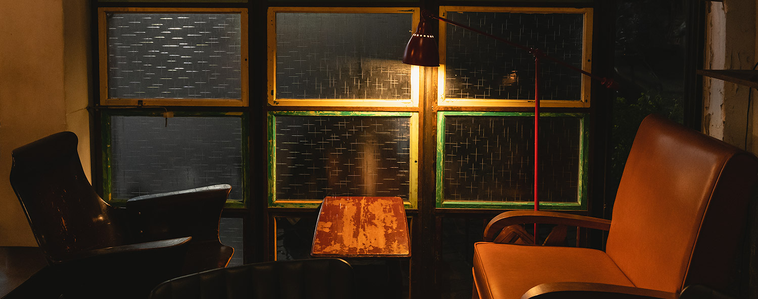 An old chair and wooden table under lamplight at the window in Gandan Cafe in Tainan