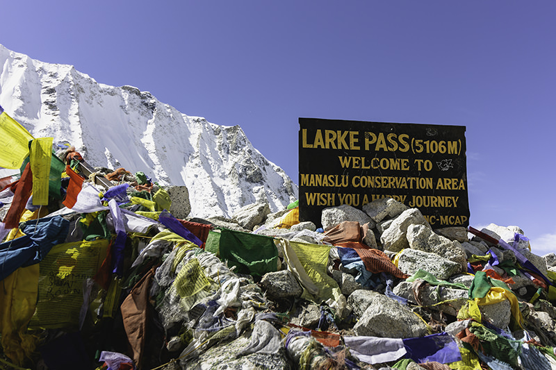 The Larke Pass sign displays the altitude, in front of blue sky and shining white mountain, surrounded by colourful prayer flags