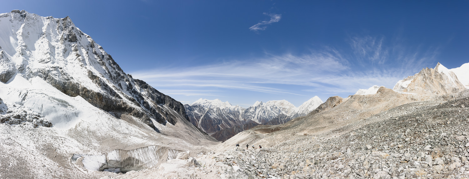 A panoramic view of the mountains looking down from Larke Pass, with the glacier visible in the foreground and tiny fugures seen descending the trail