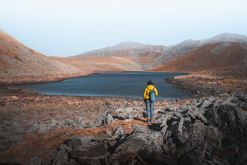 A person stands on a rock strewn slope admiring the blue water of Levani's Lake on the Javakheti Plateau
