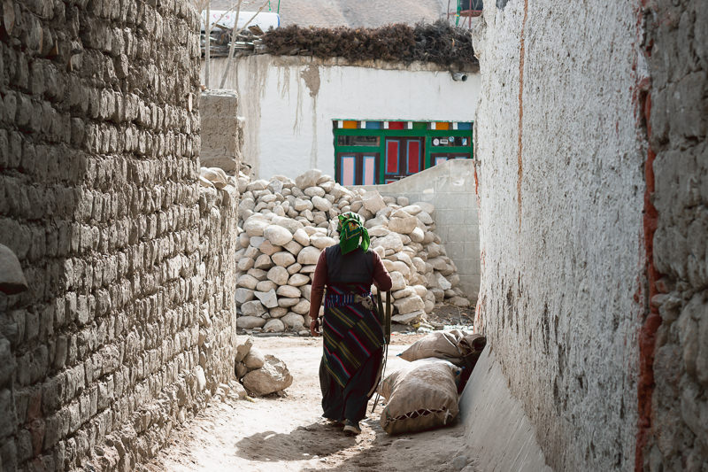 A woman in traditional Tibetan dress wandering down a narrow alley in Lo Manthang