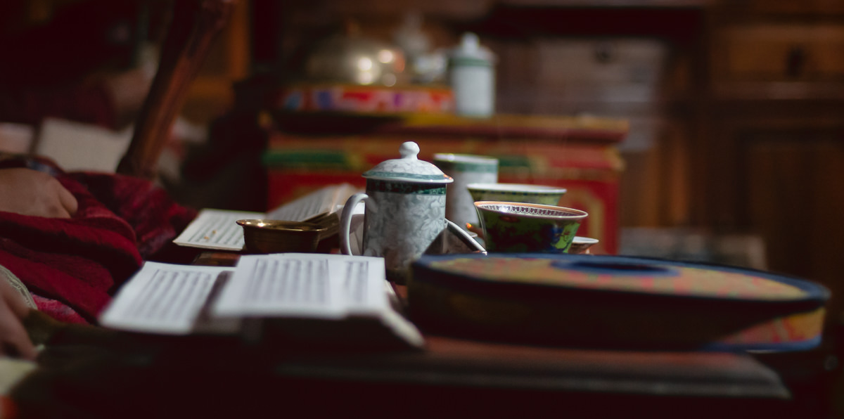 Sacred manuscripts, teacups, and the round case for a musical instrument sitting on a table while monks perform a puja ceremony in Lo Manthang