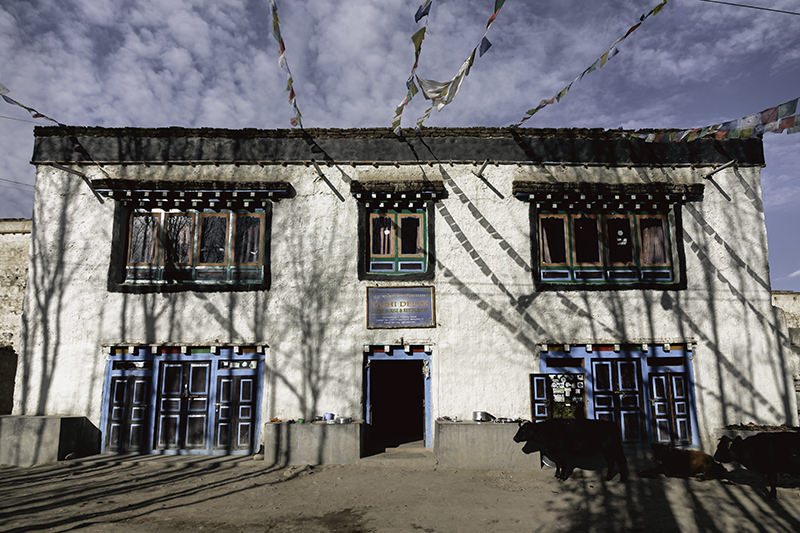 External view of the large traditional Mustang style Tashi Delek Guesthouse, with prayer flags strung from its rooftop and colourful window frames against whitewashed walls