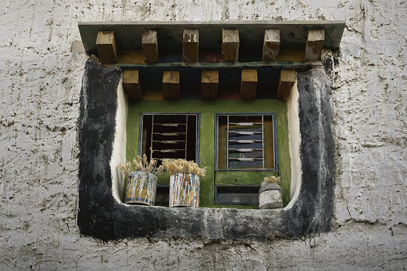 A green and orange wooden window frame with old paint tins with flowers on the window sill in Lo Manthang
