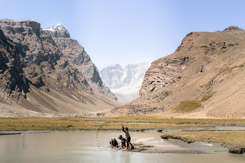 Local herder kids play at the edge of the river at Peak Engels Meadow, the mountains rising behind