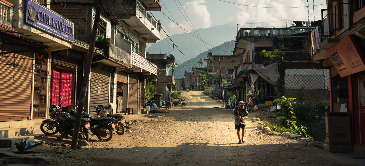 A local man carrying a load on his back down the dirt road of Arughat Bazar in Nepal