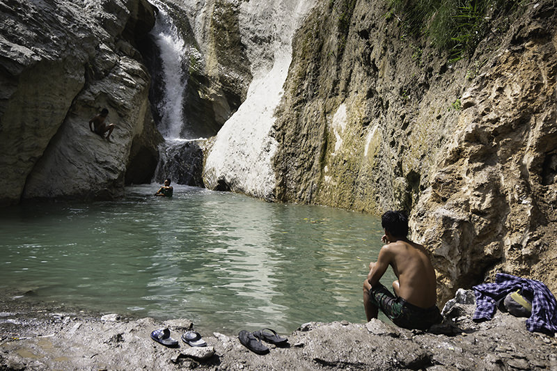 Locals swim in a pool at the side of the track near Machakhola on the Manaslu Circuit Trek. The pool is fed by a small waterfall.