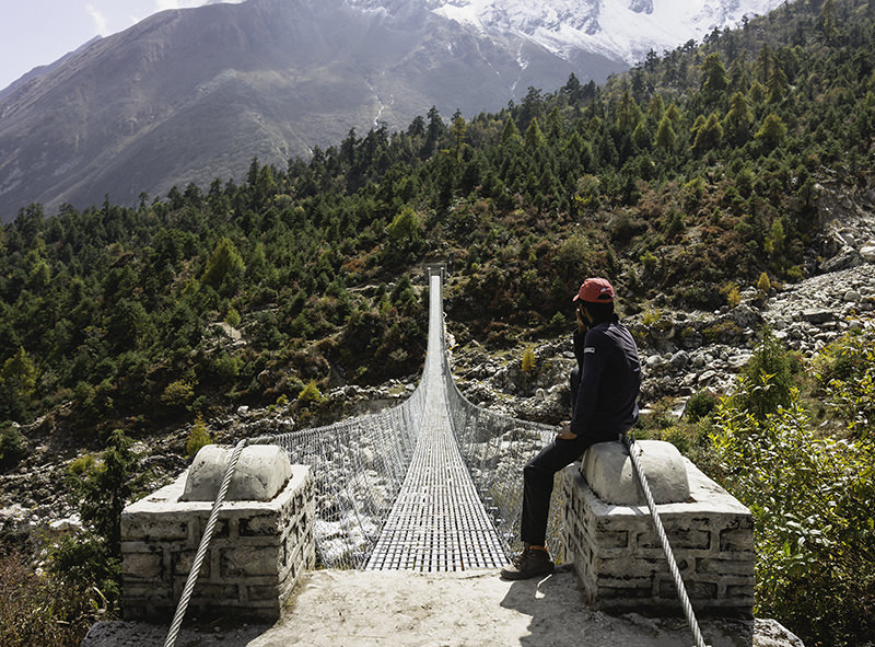 A trekking guide sits at the end of a long suspension bridge before Samagaun on the Manaslu Circuit Trek