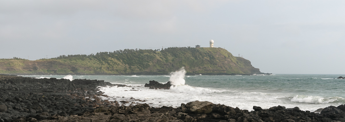 Looking back at Suweolbong in the sunshine while the waves crash in on Jeju Olle Trail Route 12