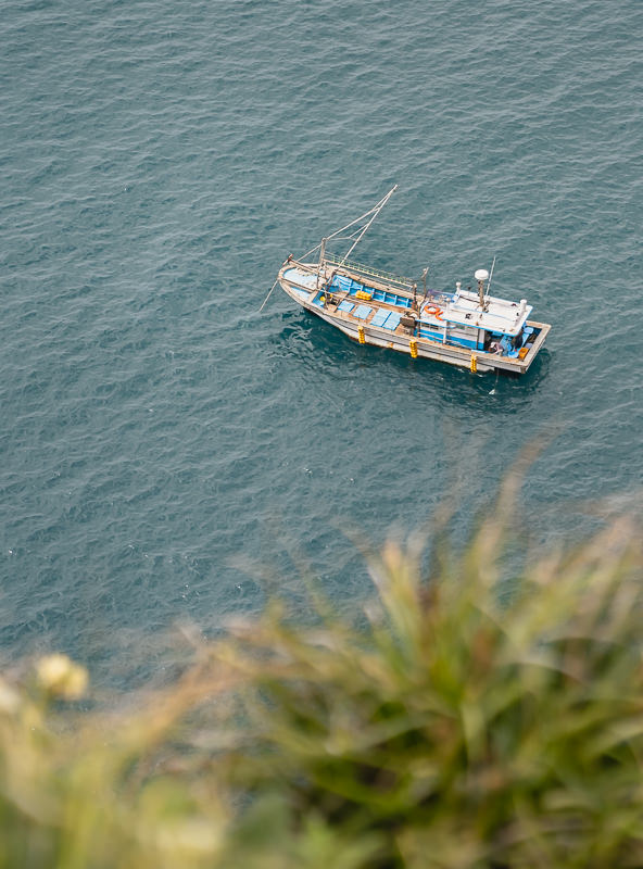 Looking down on a fishing boat from on top of the cliffs on Jeju Olle Trail Route 9