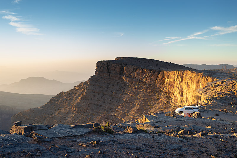 Looking down on our campsite at Jebel Shams in Oman as the rising sun hits the canyon rim