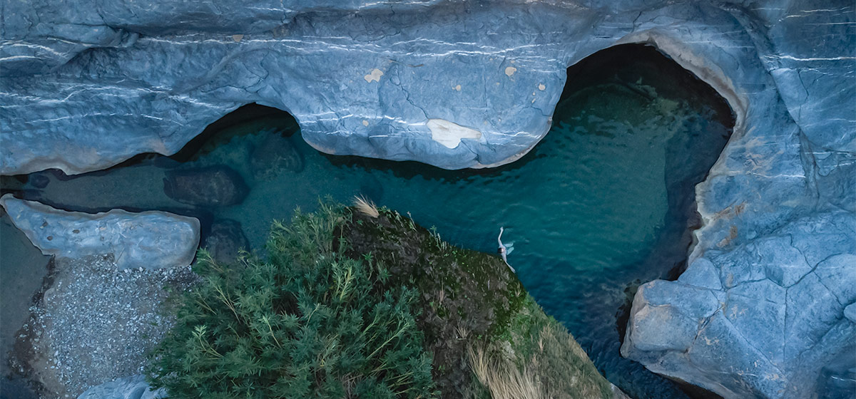 This is the reason why Wadi Damm is one of the best campsites in Oman - the hidden pool fringed by blue grey rock and green moss and ferns. The picture shows a top down aerial view of Kim swimming in the dark water.