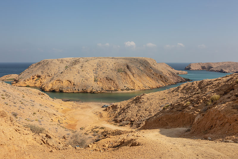 A view over the sparkling blue waters of the inlet at Bandar Al Khiran in Oman. The steep dirt track descends to one of the best wild campsites in Oman.