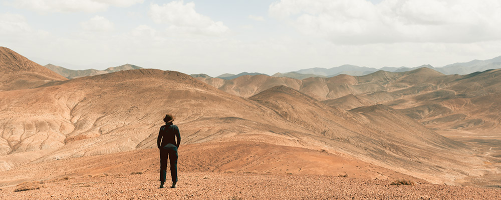 A woman standing looking out over a vast mountain landscape towards China from the viewpoint at Shorbuloq Observatory, off the Pamir Highway